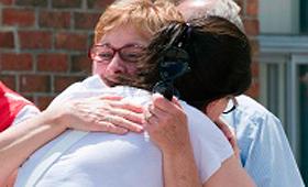 Pessoas abraçam-se no exterior de um abrigo de emergência em Lac-Mégantic, Que., - 11 de julho, 2013. (Jacques Boissinot/The Canadian Press)
