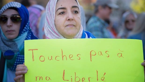Uma manifestante segura um cartaz pedindo que ninguém toque na sua liberdade, durante um protesto em Montreal contra a proposta de Carta de Valores pelo Parti Québécois - 29 de setembro, 2013. (Peter McCabe / The Canadian Press)