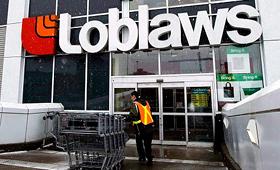 Um funcionário do Loblaws arruma os carrinhos de compras. (The Canadian Press / Nathan Denette)
