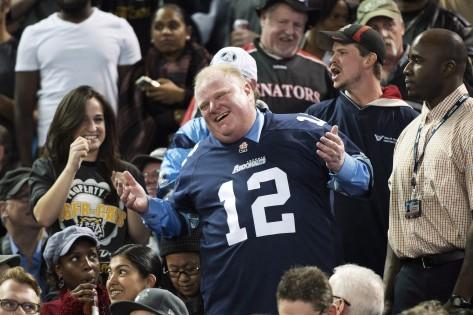 Rob Ford ri com os fãs, durante a final da Divisão Este (CFL) que envolveu os Toronto Argonautas e os Hamilton Tiger-Cats. THE CANADIAN PRESS/Nathan Denette