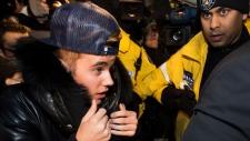 Justin Bieber cercado pelos Media e policiais, no momento em que ele se entregava à polícia da cidade de Toronto - 29 de janeiro, 2014. (Nathan Denette / THE CANADIAN PRESS)
