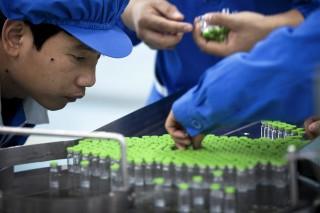 Trabalhadores inspecionam rótulos em frascos contendo a vacina contra a gripe H5N1, na Sinovac Biotech Ltd., em Pequim, China. Foto de arquivo. AP Photo/Andy Wong.