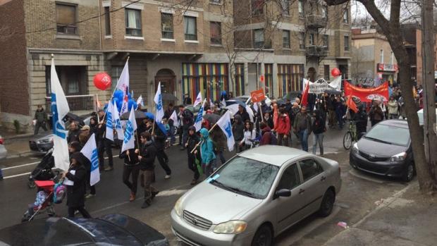 Centenas de pessoas caminham à chuva em Montreal para apelar ao fim da austeridade e pedir um aumento no salário mínimo.